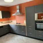 Réalisations Cusines DEBARD - Plan de travail bois, meubles anthracites et murs rouges
