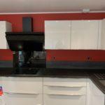 Réalisations Cusines DEBARD - Murs rouges, hotte décorative, meubles blancs et plan de travail anthracite