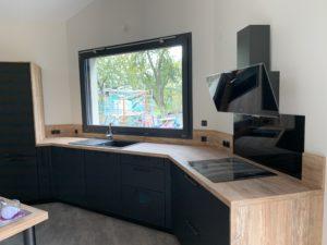 Réalisations Cusines DEBARD - Cuisine asymétrique, hotte décorative meubles gris foncé et plan de travail bois clair
